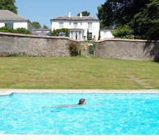 Outdoor heated swimming pool in walled garden